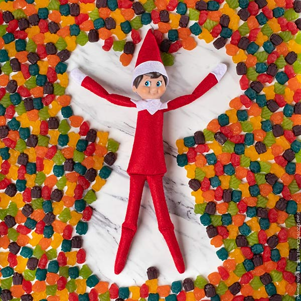 Elf making a snow angel out of fruit snacks
