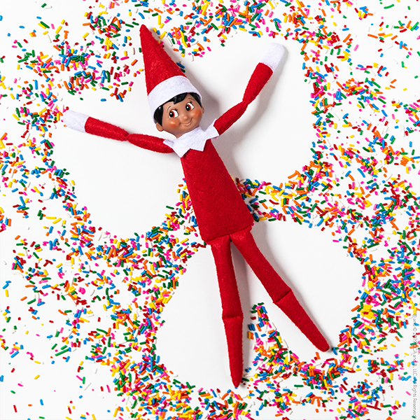 Elf making snow angel in sprinkles