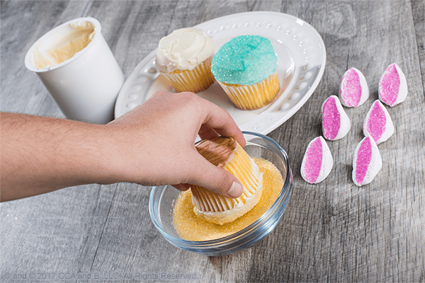 Dip frosted cupcake top into sprinkles for Easy Easter Bunny Cupcakes