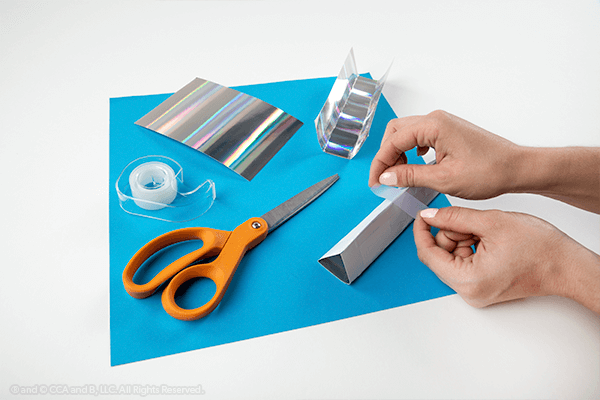 Hand taping paper into triangle tube
