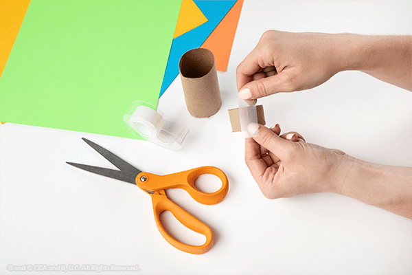 Hands taping paper towel tube end
