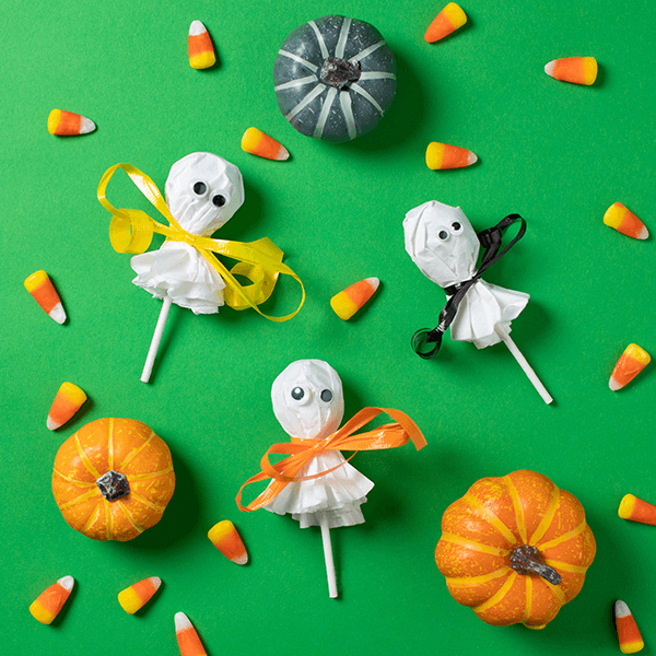 Ghost pops on green background with candy corn