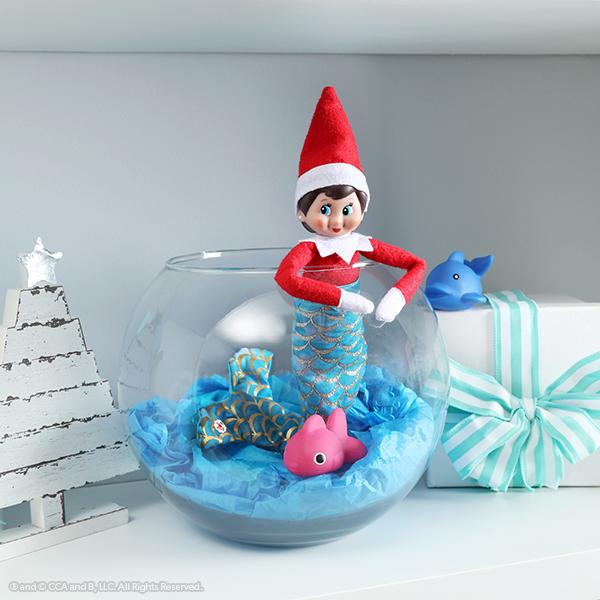 Elf in mermaid outfit in fishbowl