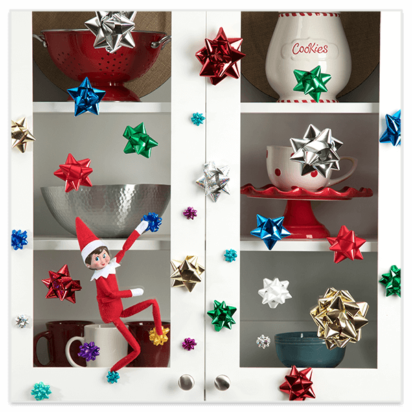 Scout elf climbing cabinet on gift bows