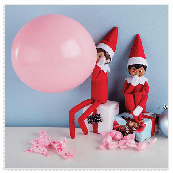 Scout elf blowing up pink balloon