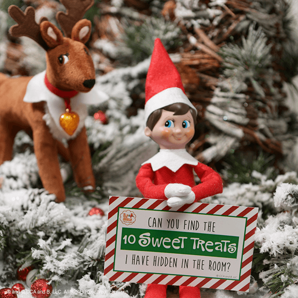 Elf and reindeer with sweet treats sign