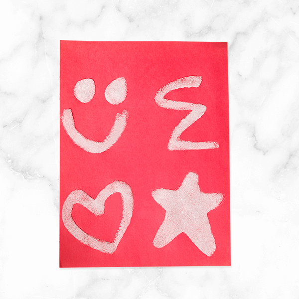 Invisible ink craft with red paper and dried salt