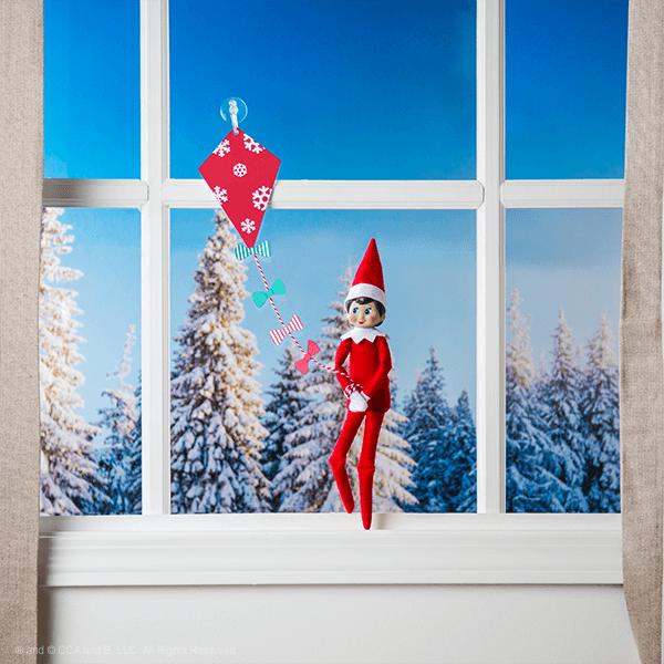 Elf in window flying a kite