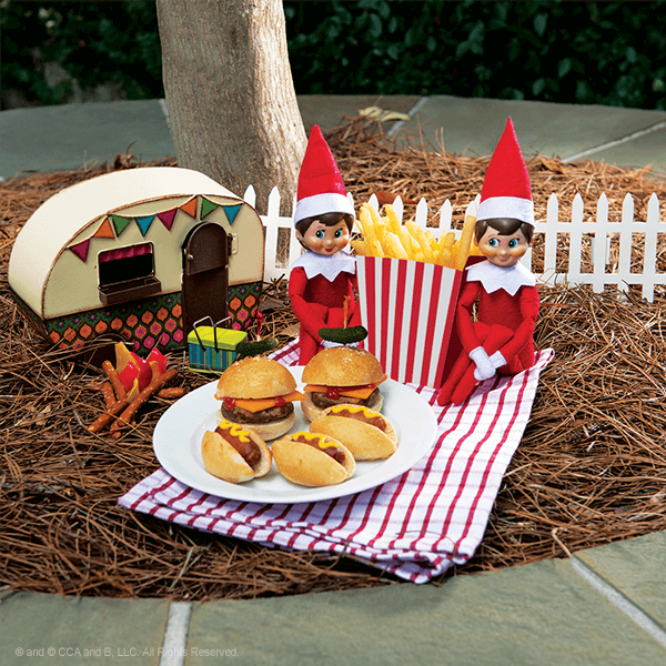 Two elves with mini burgers and hot dogs