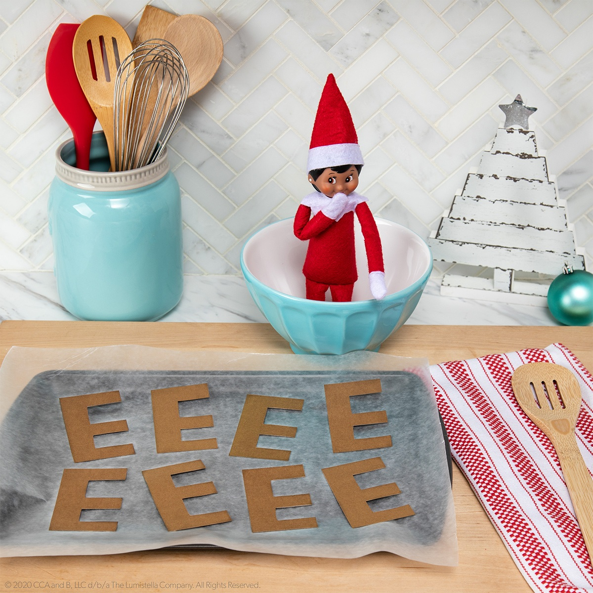 Elf with baking sheet of brown E's