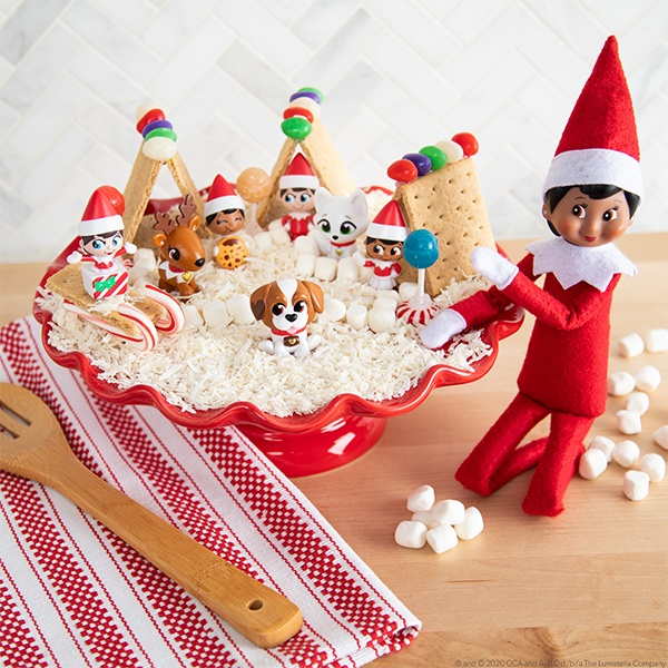 Elf with plate of mini gingerbread houses