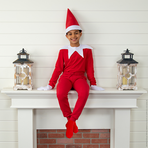 Boy in Scout Elf costume sitting on mantle