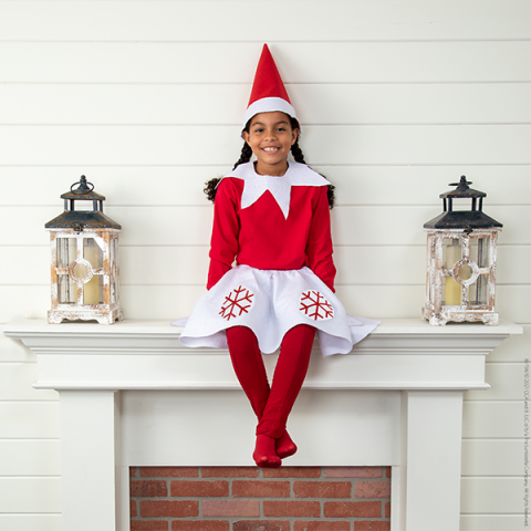 Girl in Scout Elf costume (with skirt) sitting on mantle